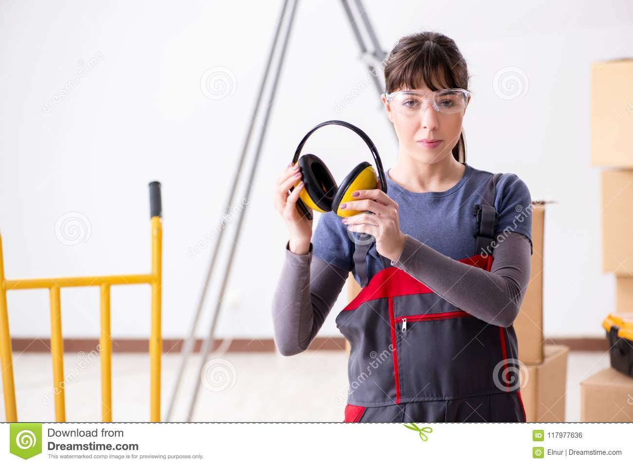 The woman contractor worker with noise cancelling headphones