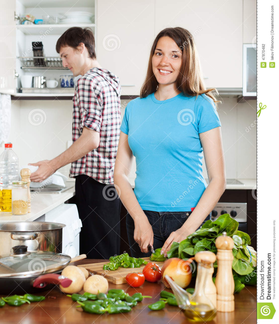 Women Kitchen: Woman Cooking Food While Man Washing Dishes Stock Photo