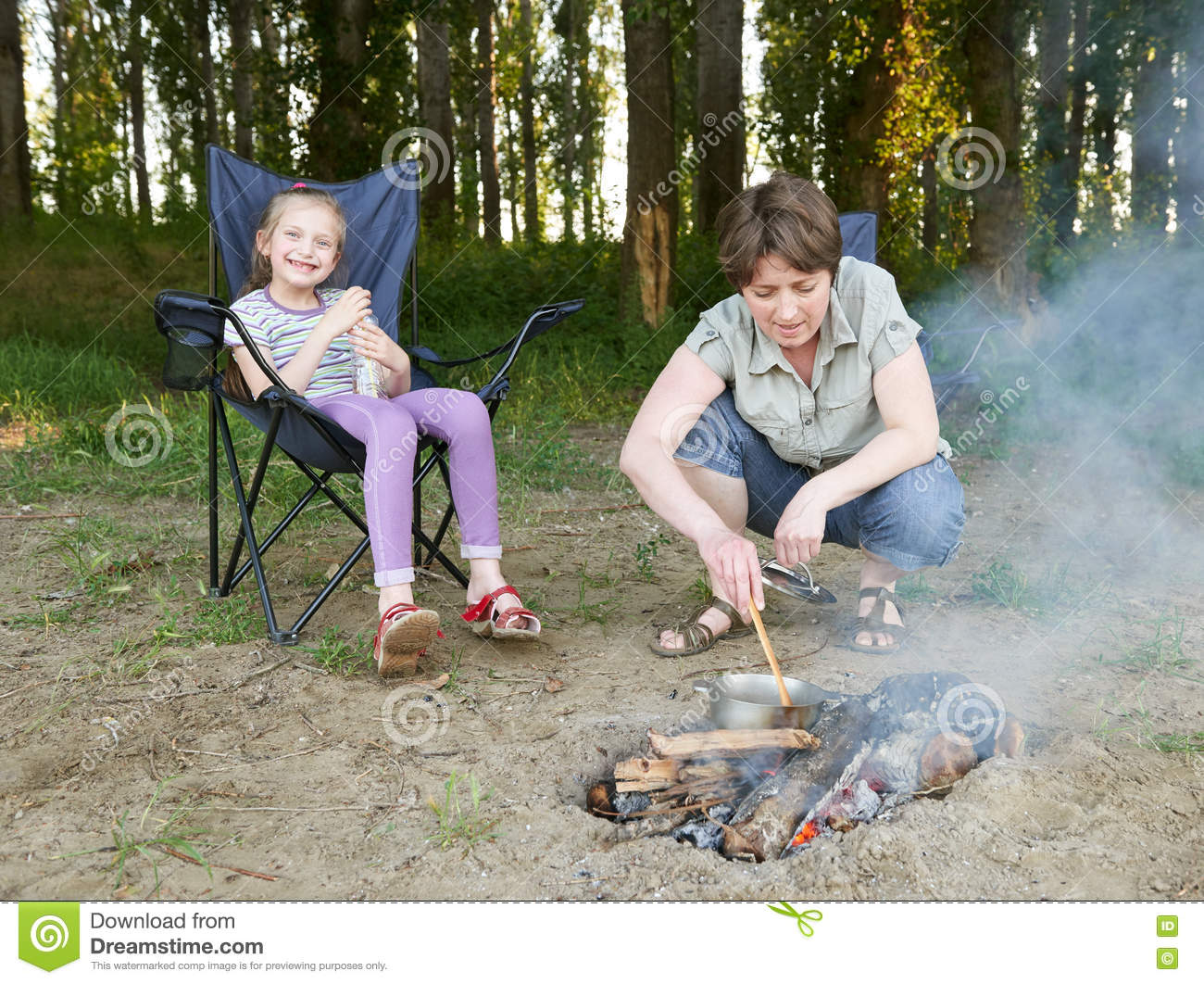 Woman cooking food, people camping in forest, family active in nature, child girl sit in travel seat, summer season