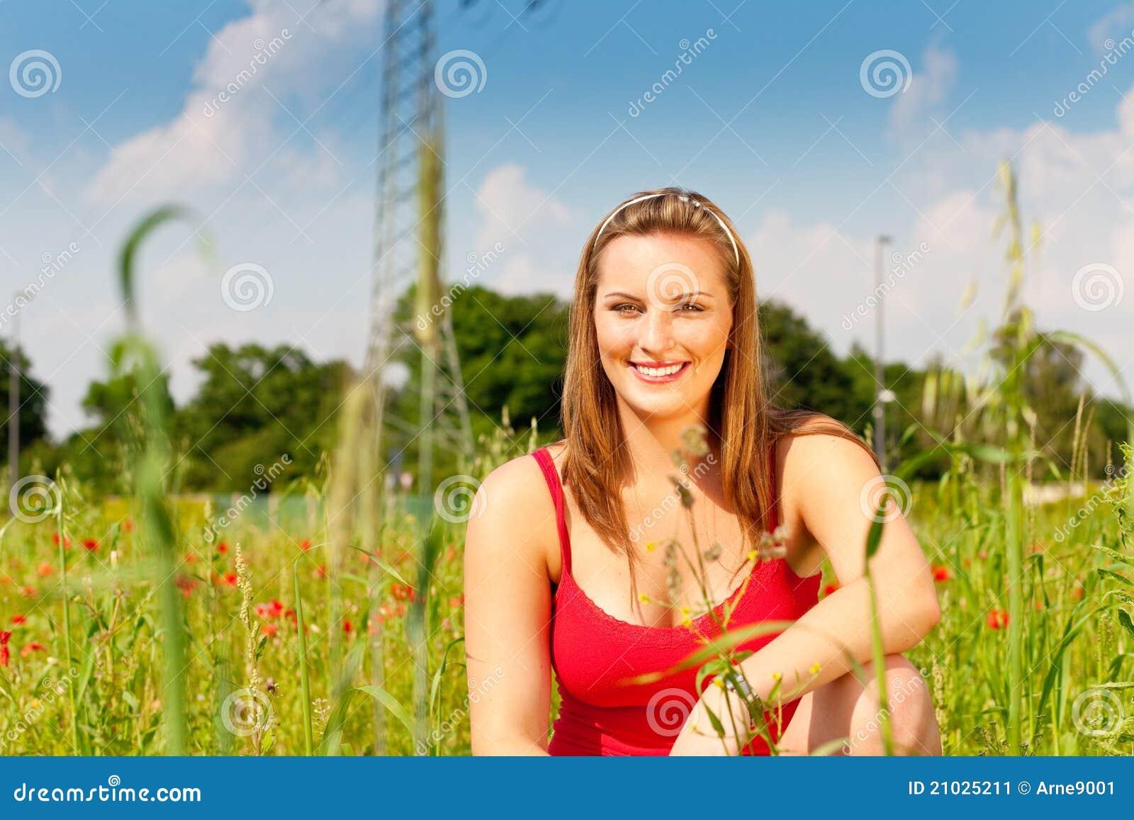 Woman cowering in meadow of field