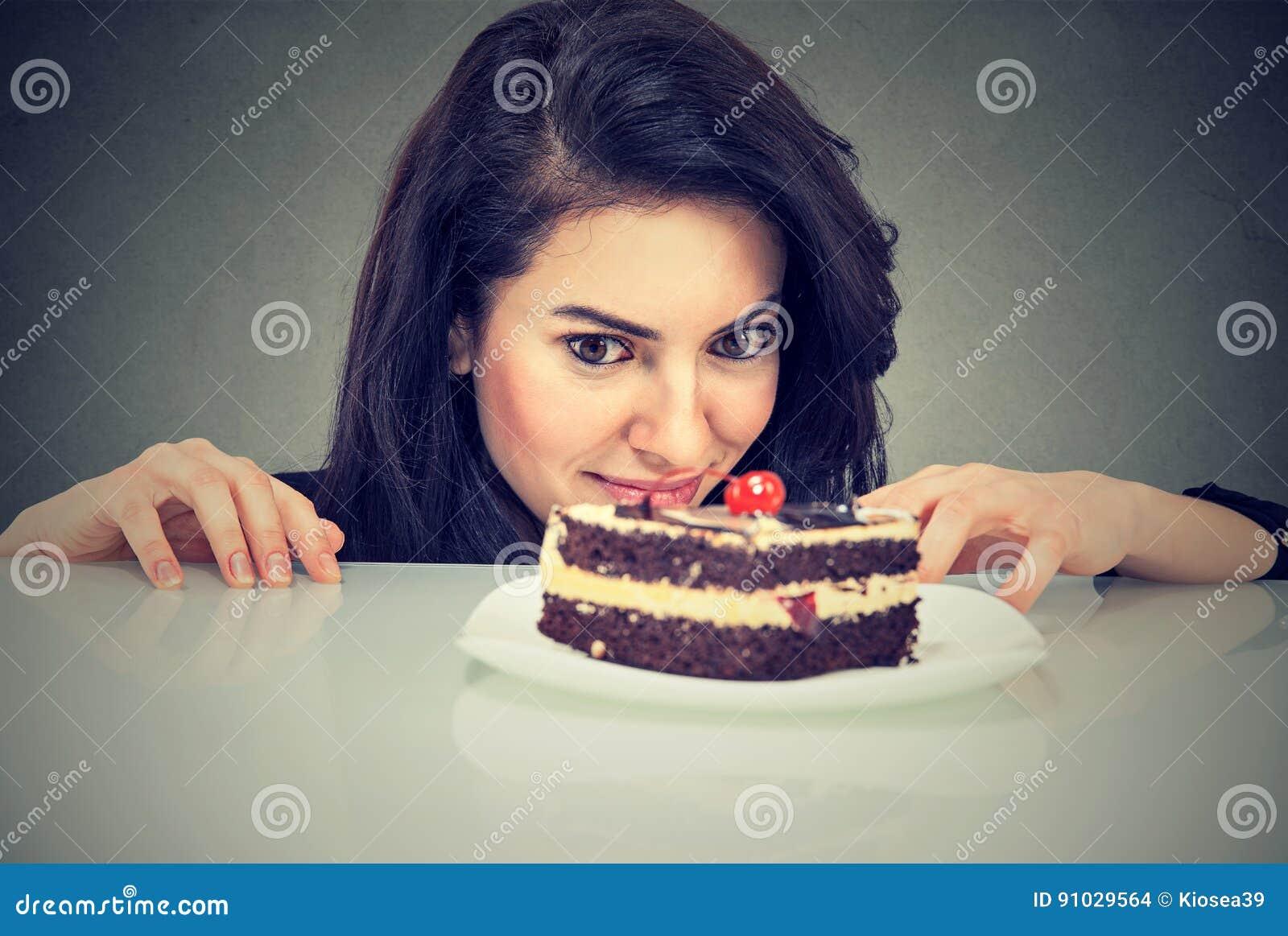 Woman craving cake dessert, eager to eat sweet food