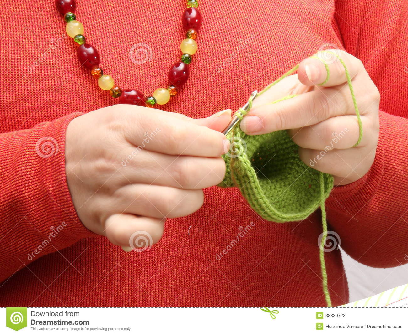 Crocheting Using Your Hands : Womans hands crocheting with green yarn and crochet hook.