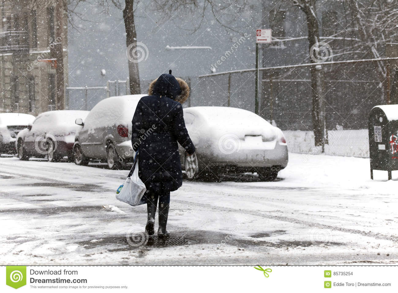 Woman crossing street during snow storm