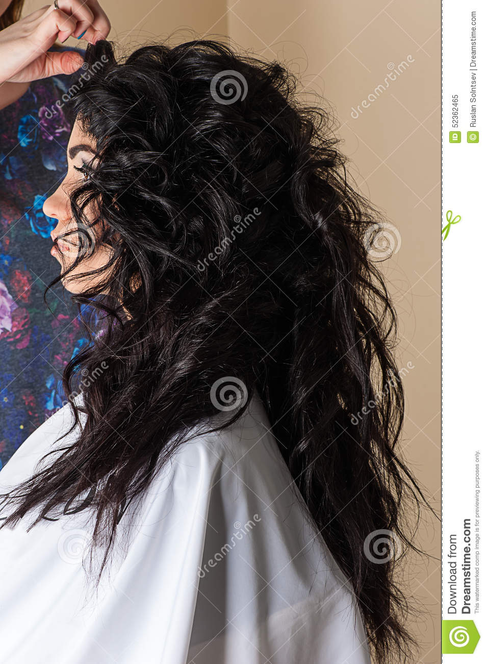 Woman with curly hair luxuriant in hair salon.