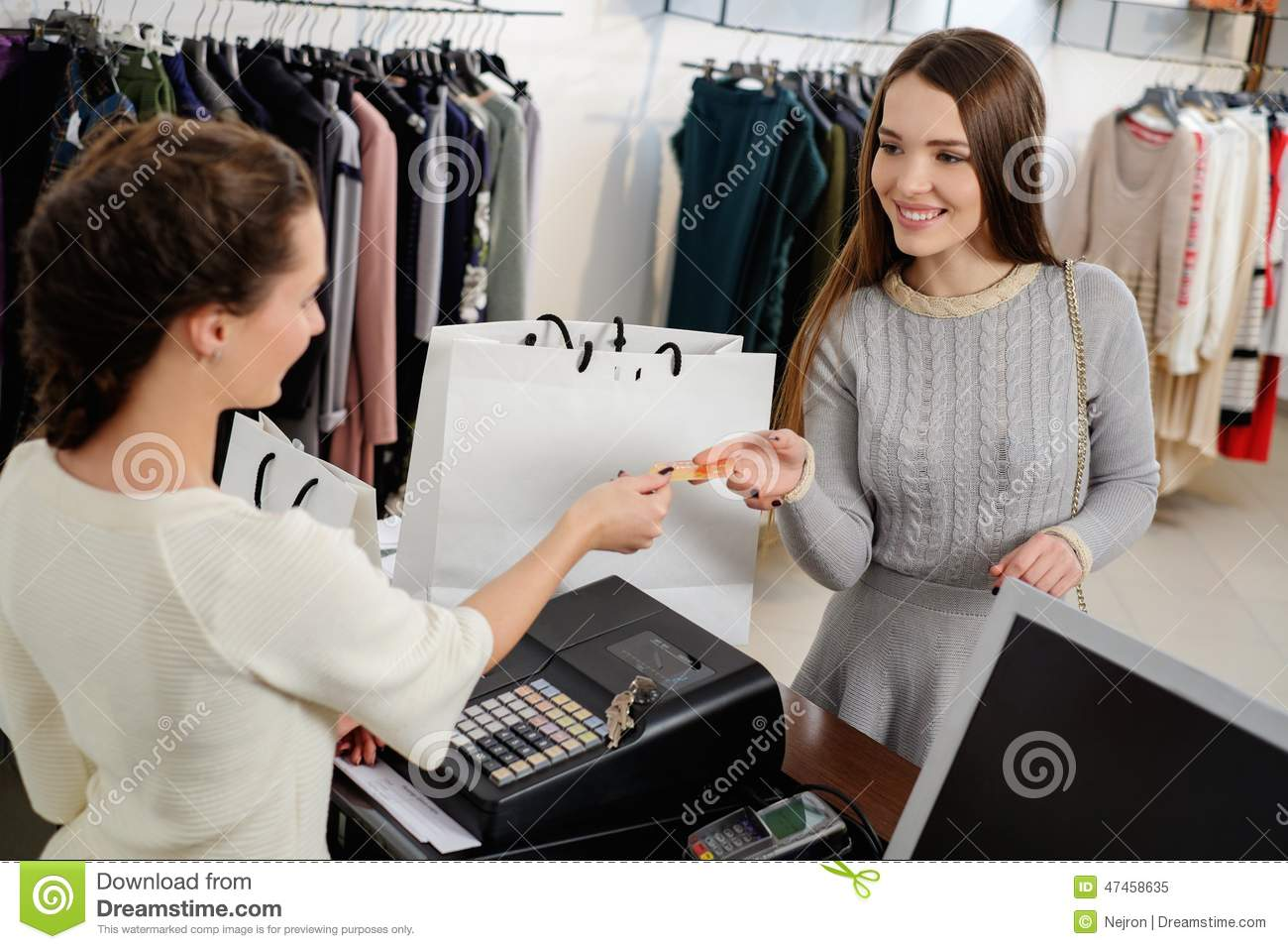 Woman Customer Paying With Credit Card In Showroom Stock