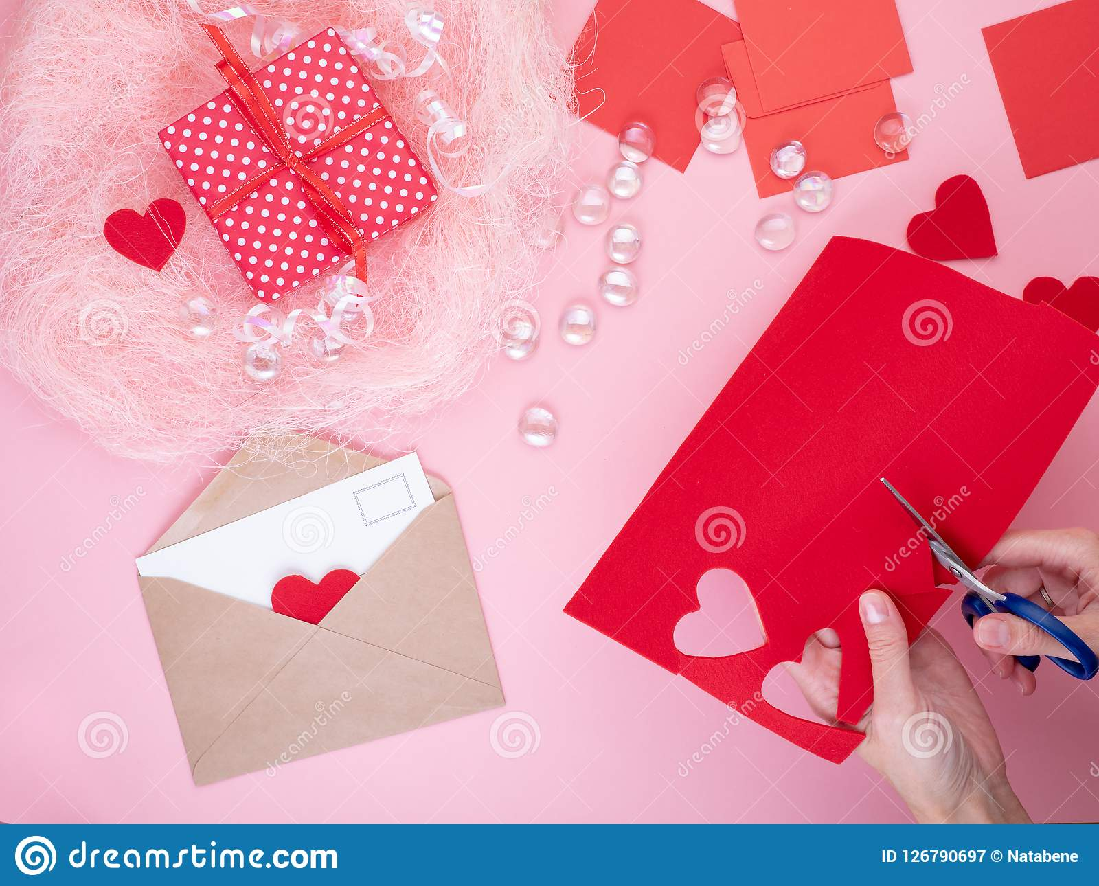 Woman cuts out red felt hearts, homemade crafts for Valentine`s
