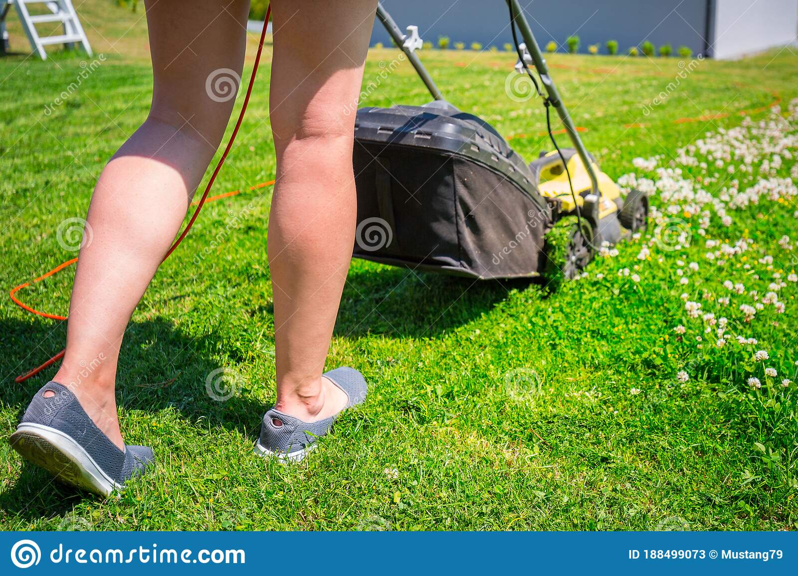 Closeup Of Woman Cutting Grass With Lawn Mower High-Res