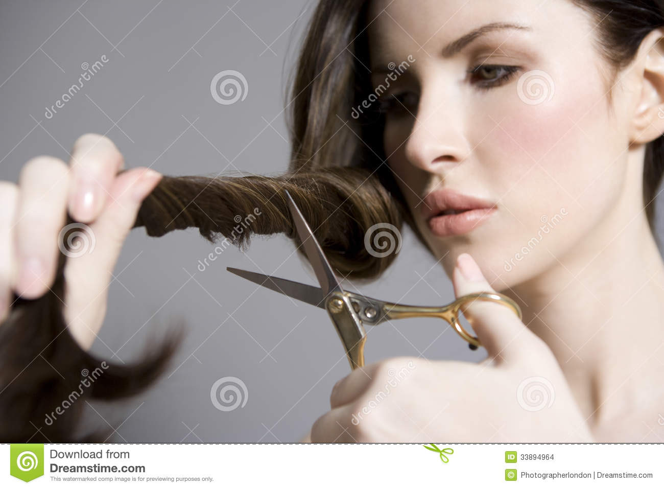Beautiful Hair Cutting : Closeup of a beautiful young woman cutting her long hair against gray ...