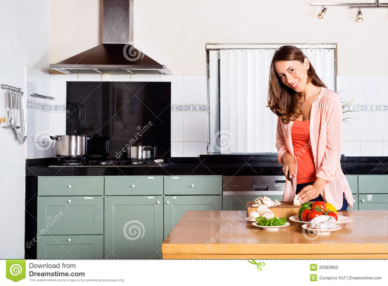 Woman Cutting Vegetables At Kitchen Counter
