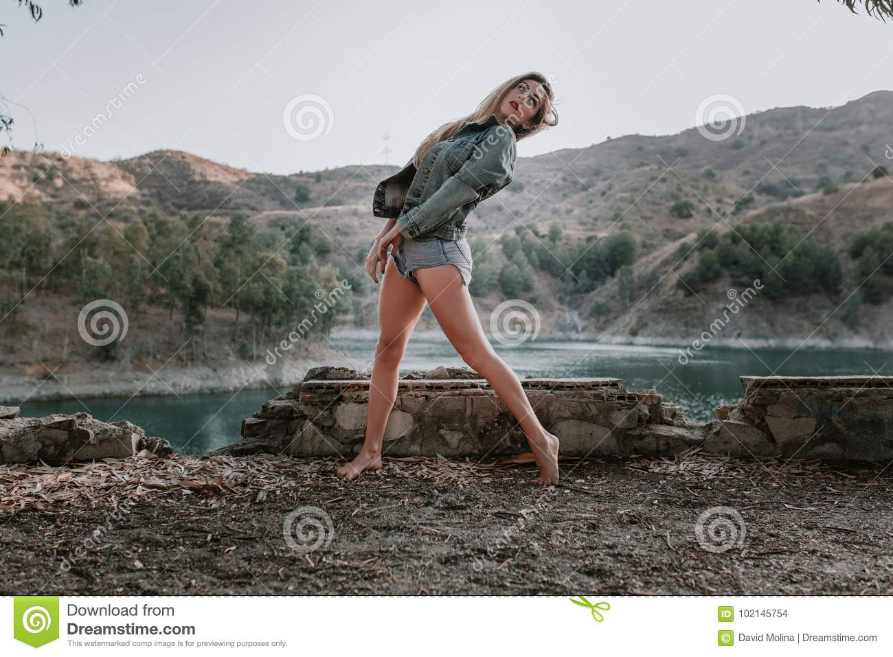 Woman in shorts and jacket posing in nature.