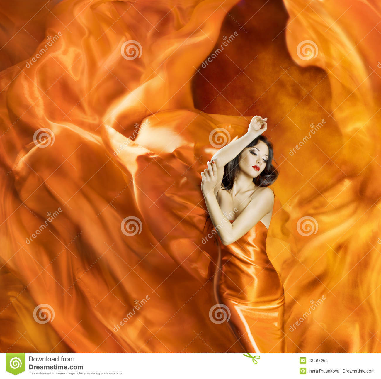 Woman dancing silk dress fire flame artistic orange burning blow