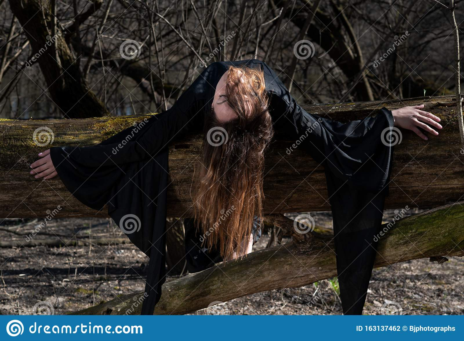Woman With Dark Long Hair In Black Robes Hanging On Tree Branches In The Middle Of The Forest Back To Nature Concept Witch Stock Photo Image Of Fantasy Concept 163137462