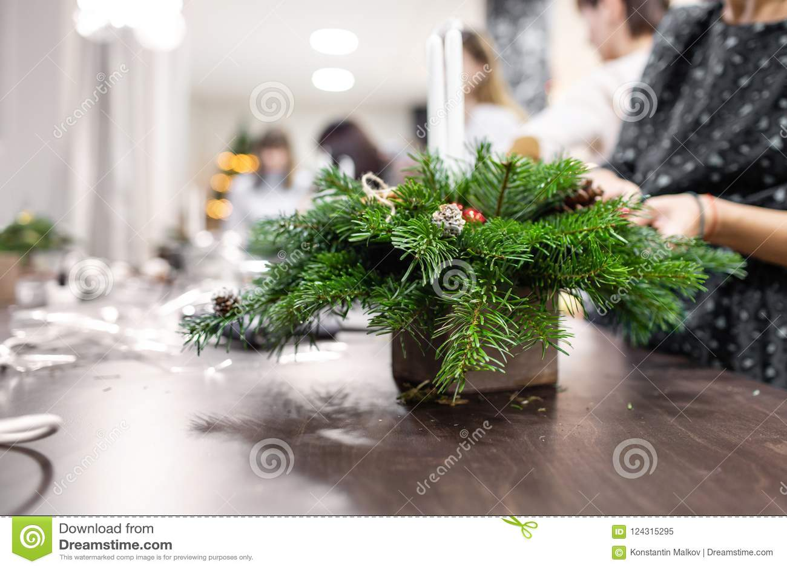 A Christmas Arrangement.A Woman Decorates A Christmas Arrangement With Candles
