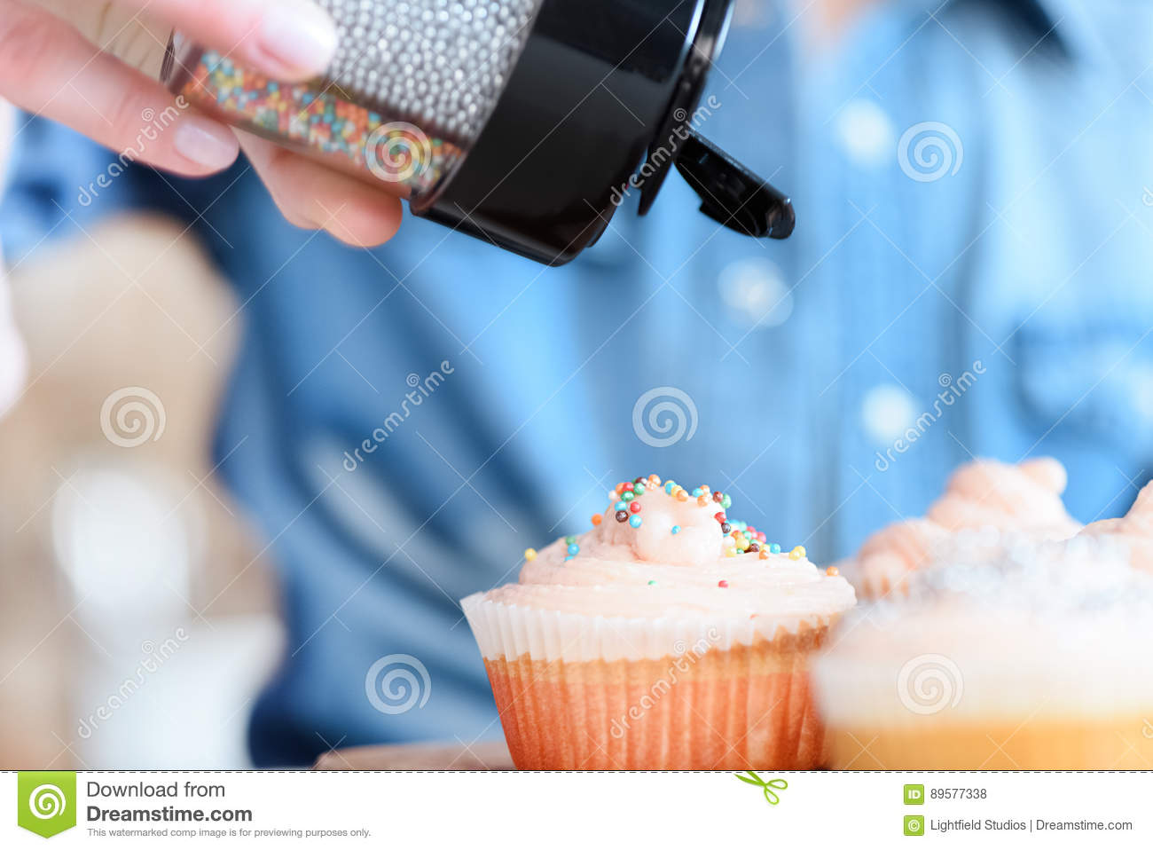 woman decorating cupcakes with confetti - Woman Decorating Cupcakes
