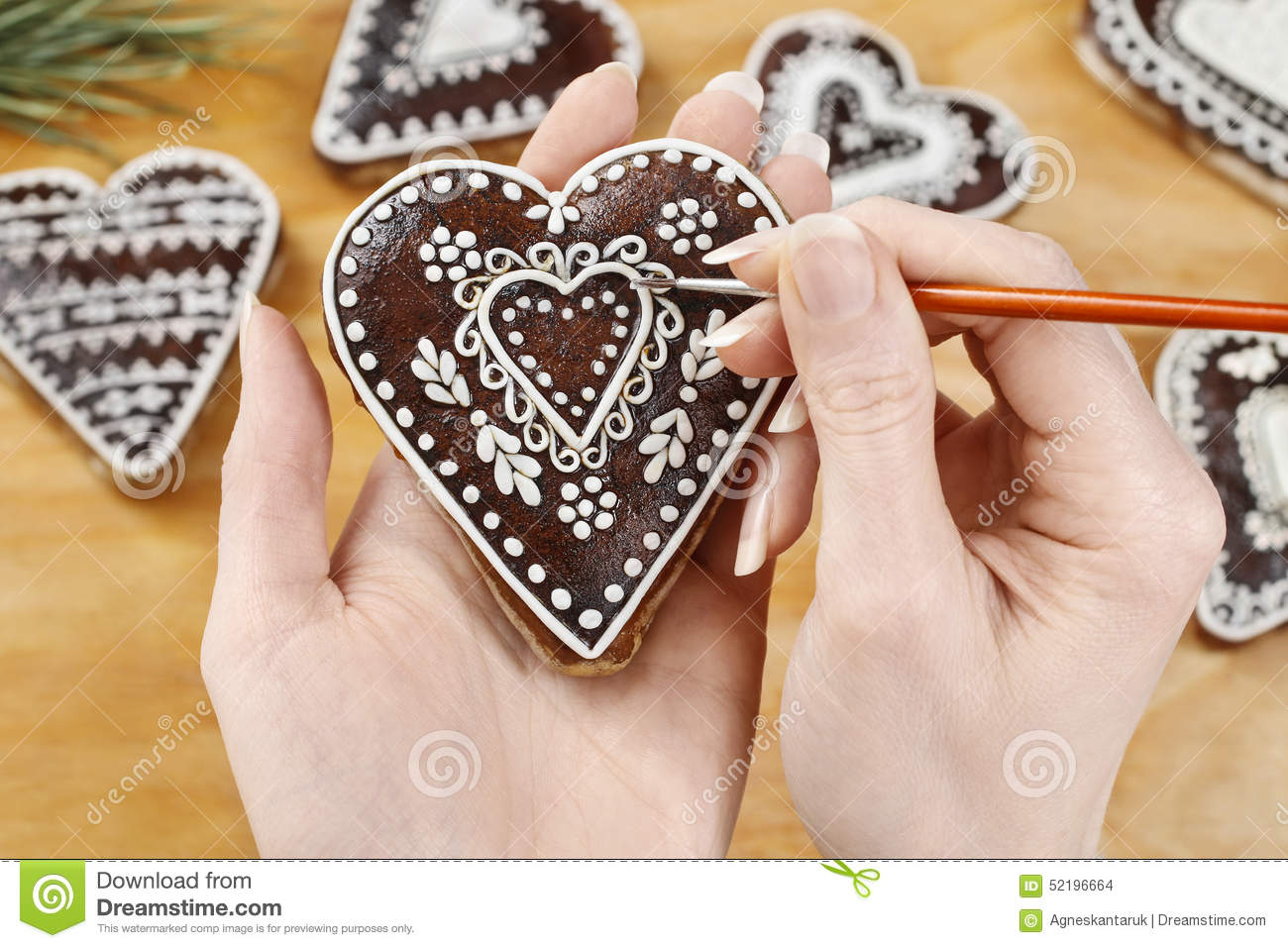 Woman Decorating Gingerbread Cookies In Heart Shape Stock Photo