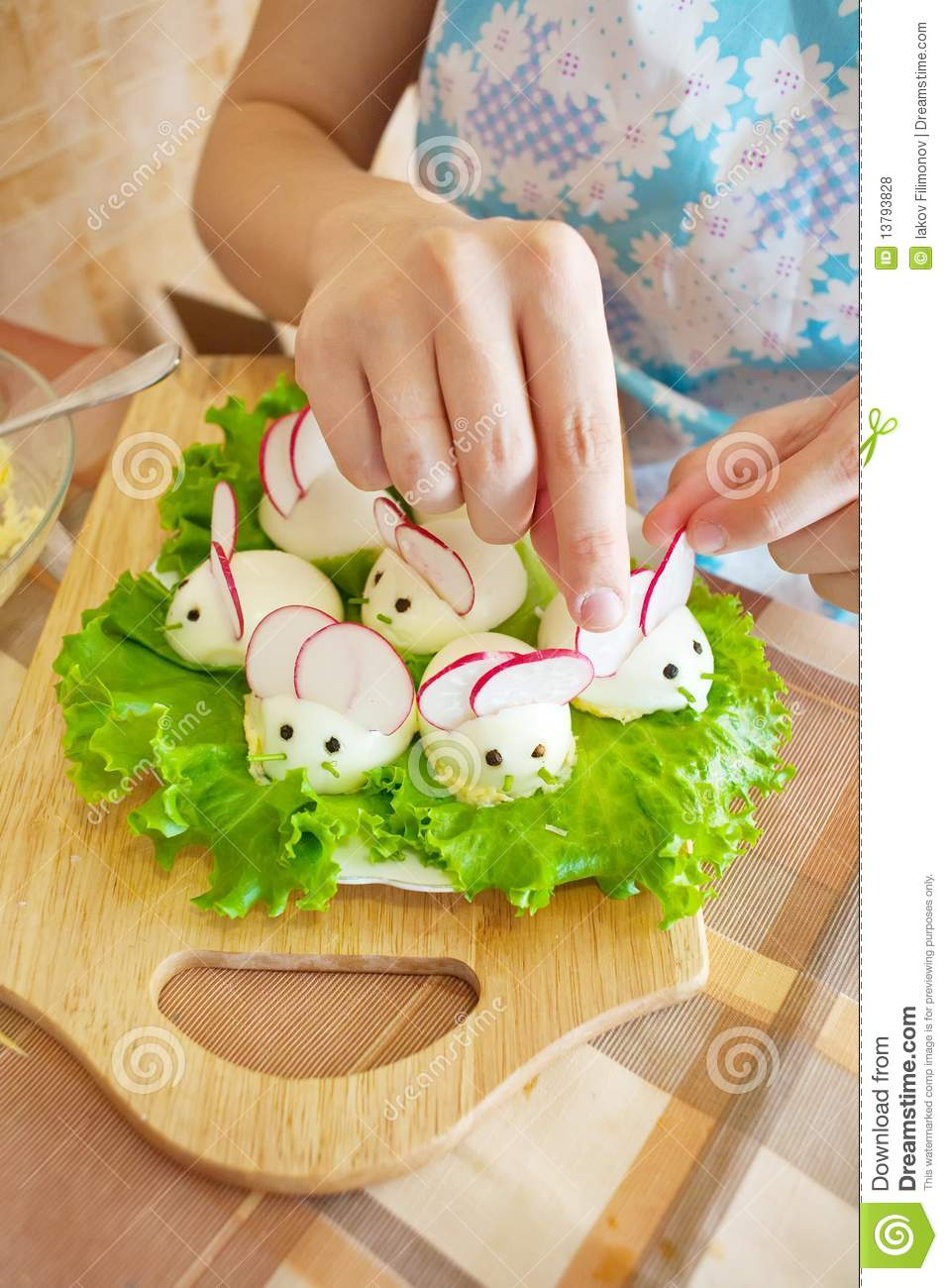 Woman is decorating stuffed eggs look like mouses