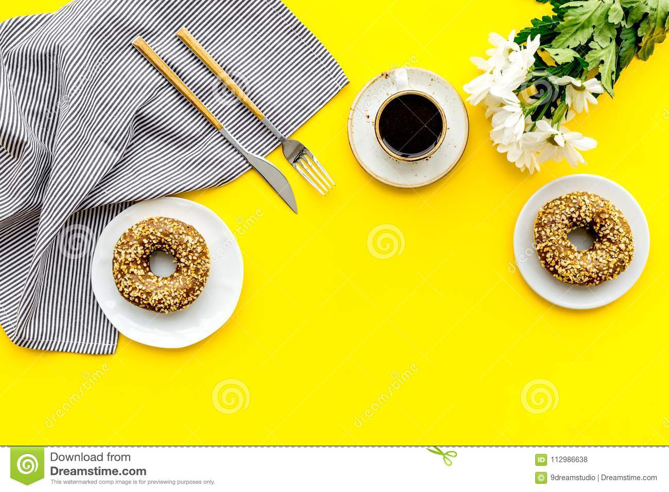Woman desk with flowers, coffee and donuts for breakfast in spring desing yellow background flat lay mock-up