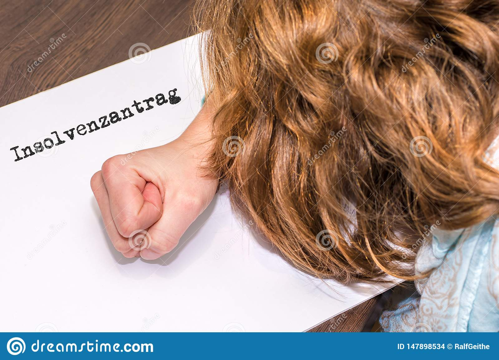 Woman gives up business and files for bankruptcy with paper on which the german word for bankruptcy petition stands