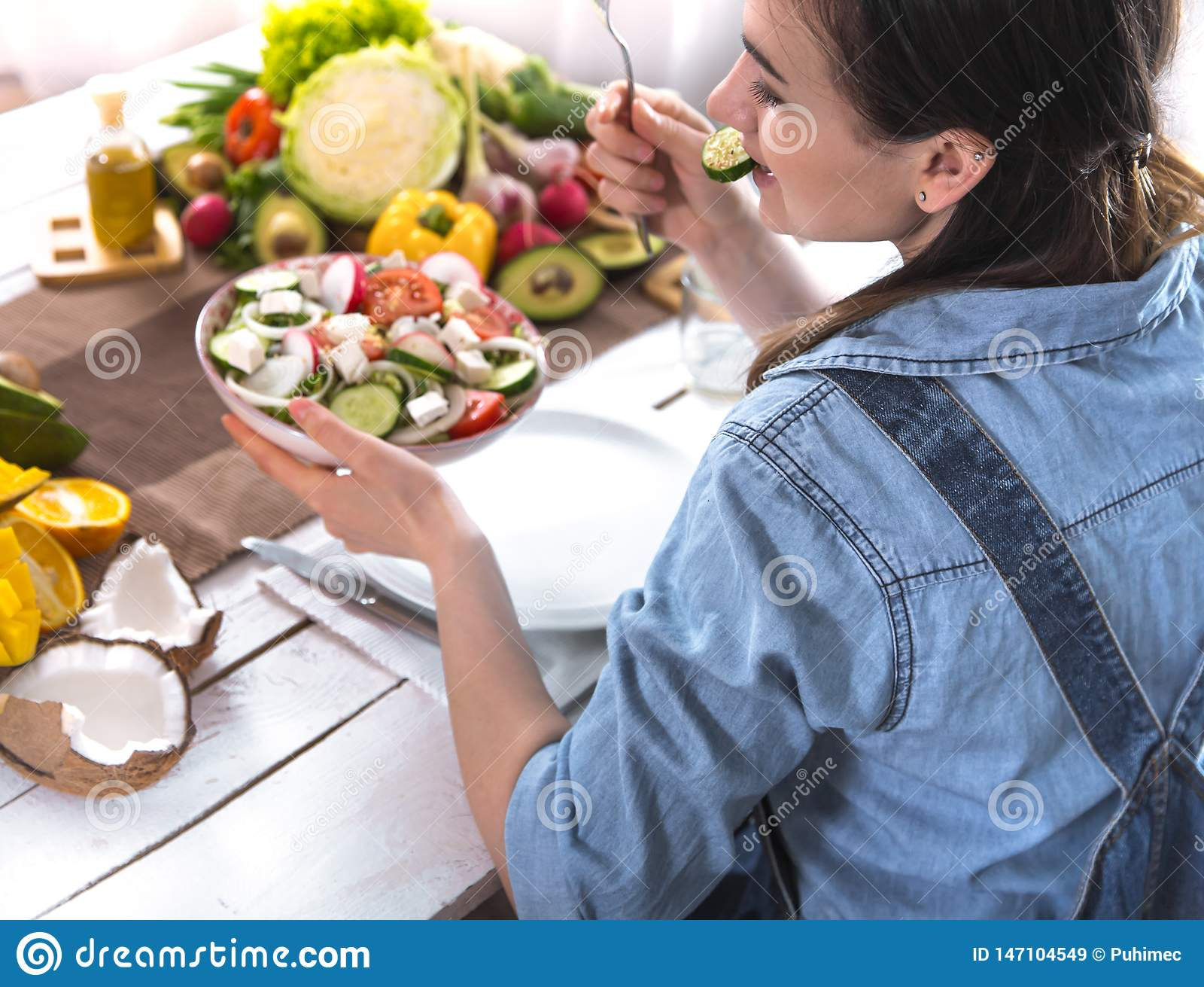 Woman at the dinner table eating salad, top view