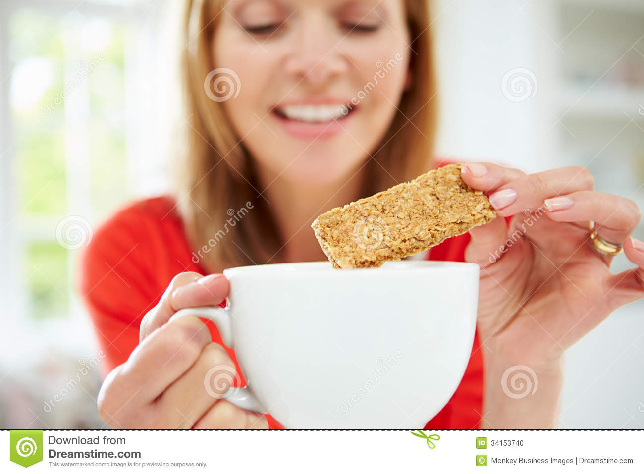 Woman Dipping Biscuit Into Hot Drink At Home Stock Photo - Image ...