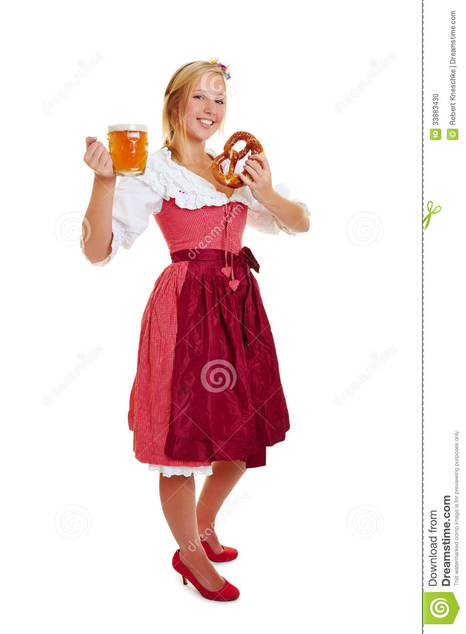 Woman in dirndl with beer and pretzel