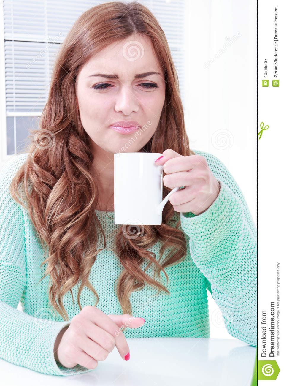 Woman disgusting smell of coffee with face expression
