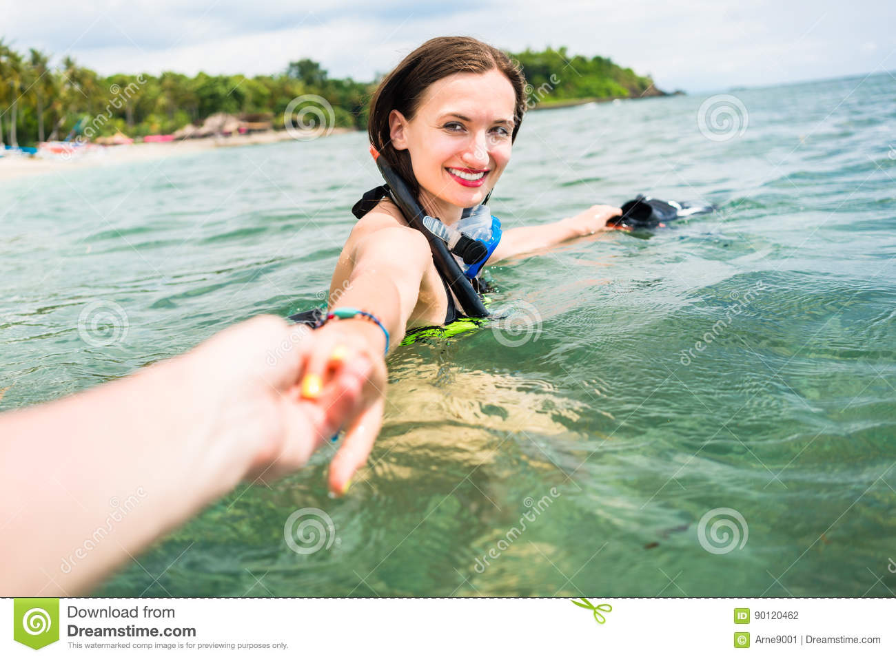 Woman with diving googles dragging partner to the sea