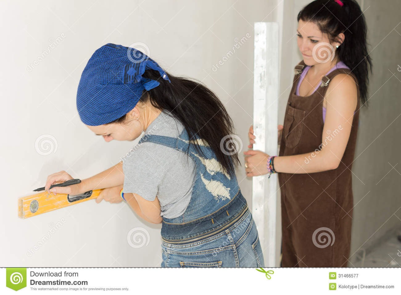 Woman DIY drawing a straight line on a wall