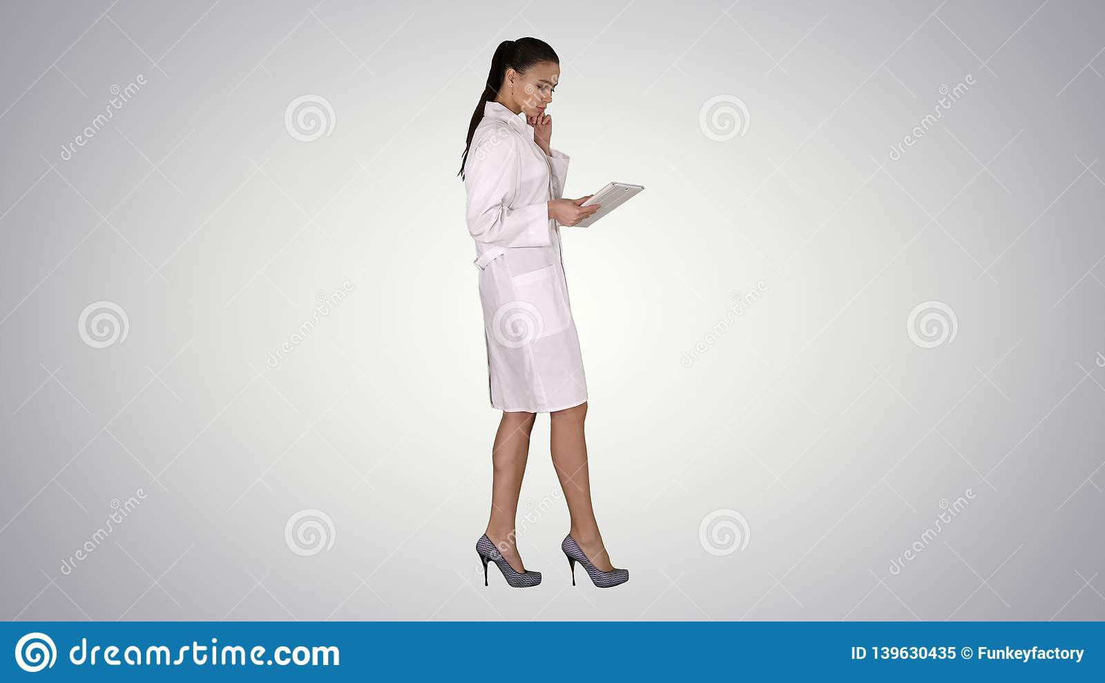 Woman doctor using tablet pc and walking on gradient background.
