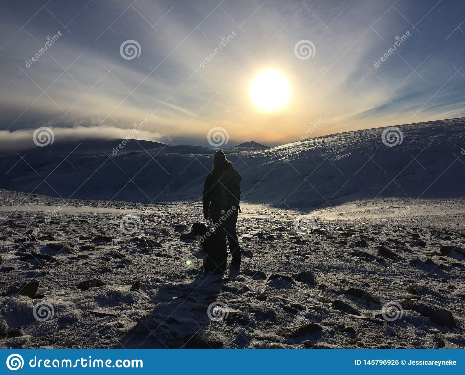 Woman and dog hiking in the mountains