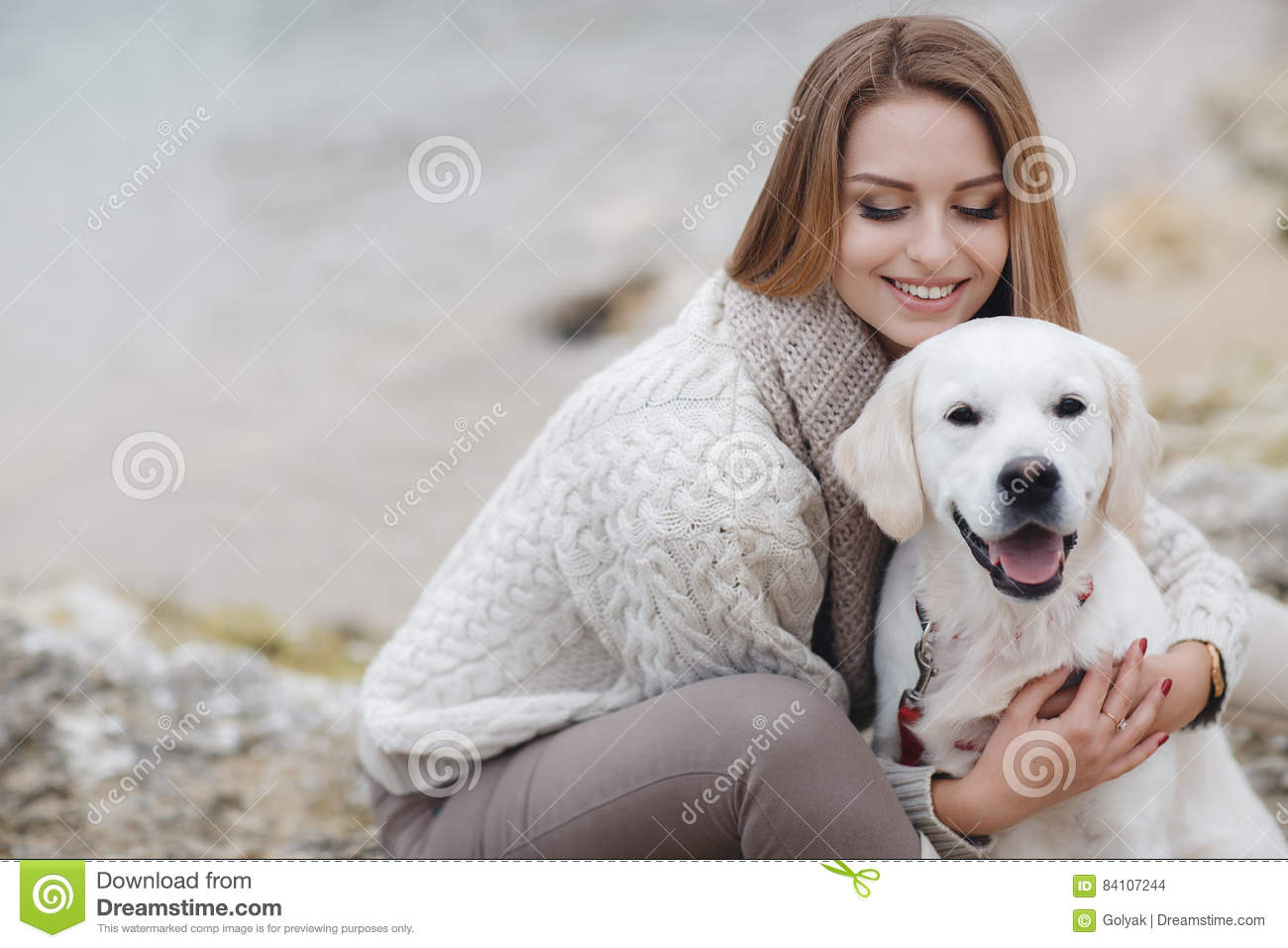 Woman with dog on the sea shore