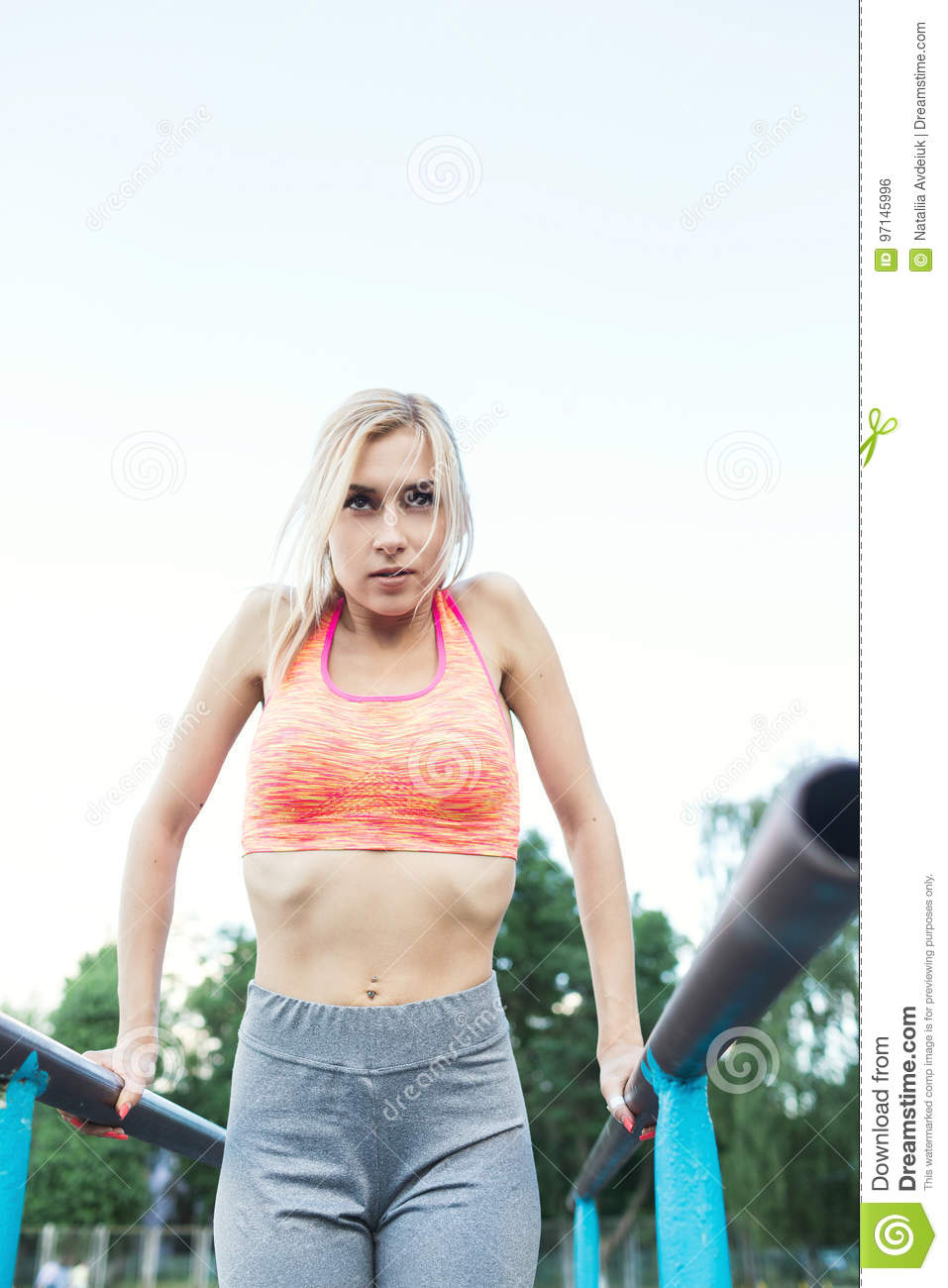 c919a802c70c7 Woman doing lifting up on the gym bar. young fitness girl pulls up on street