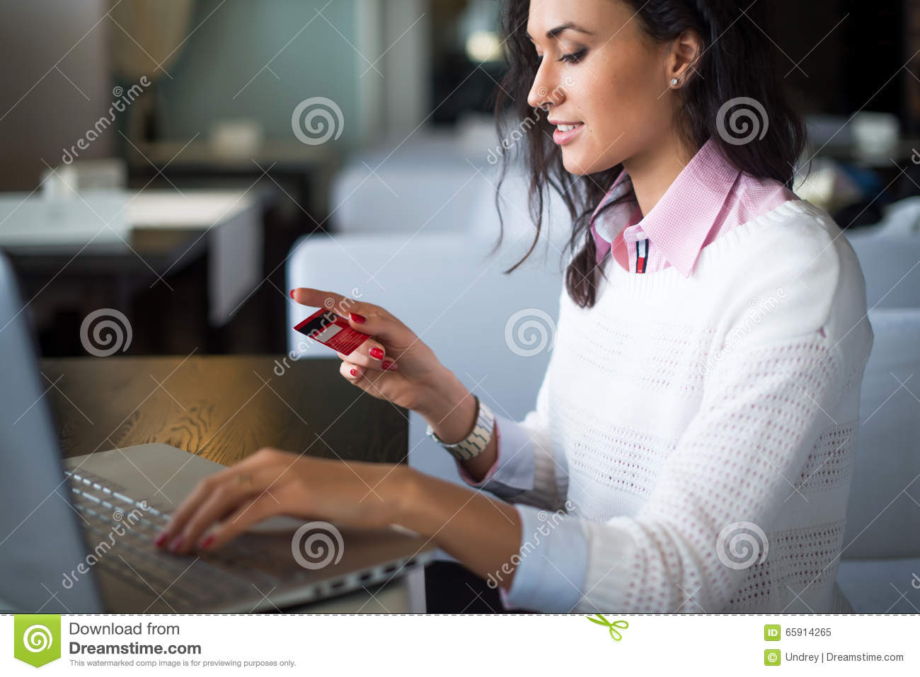 Woman doing online shopping at cafe, holding credit card typing numbers on laptop computer side view