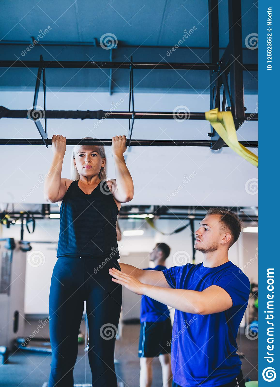 Woman doing pull-ups and a man securing her.