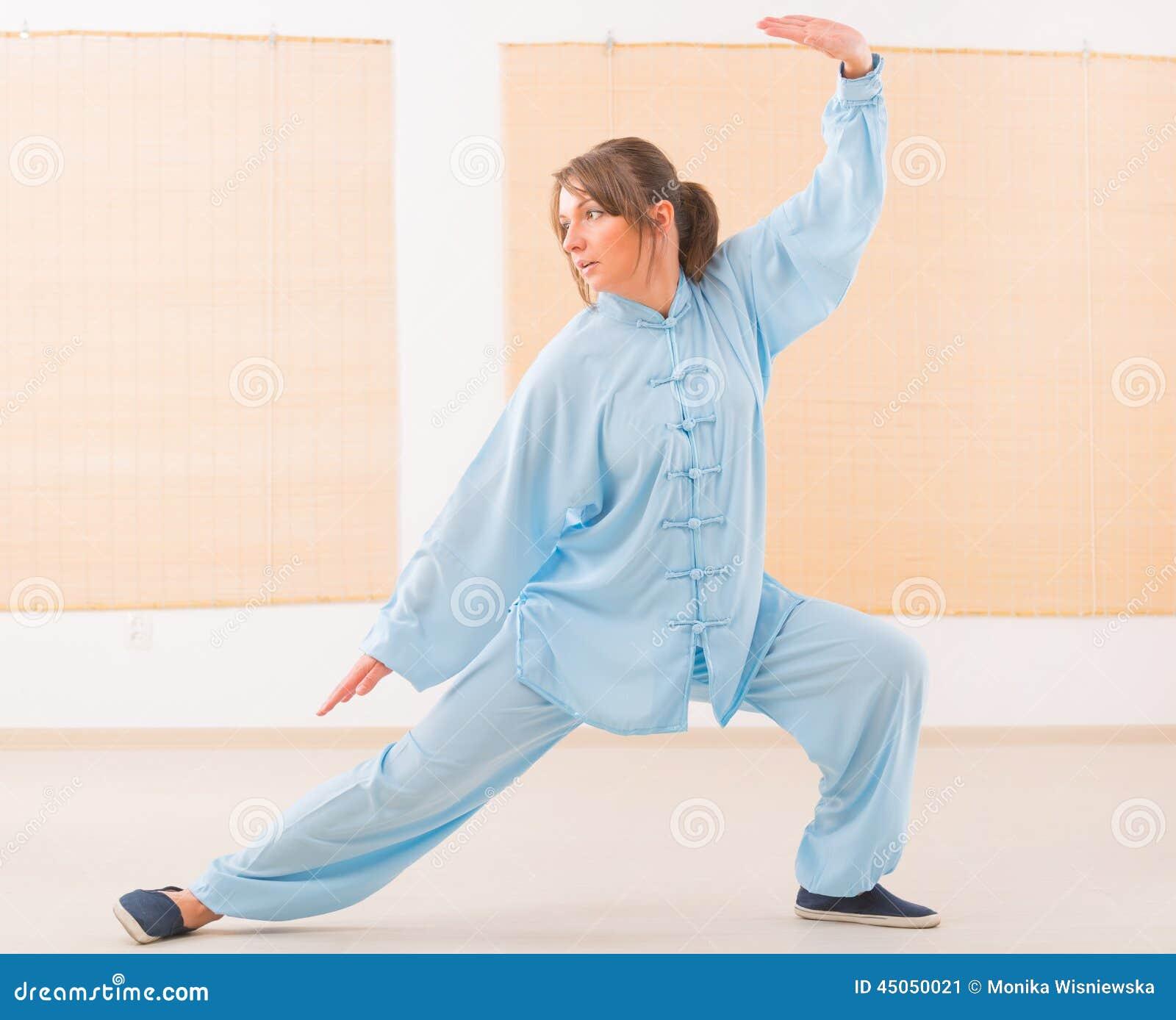 Beautiful woman doing qi gong tai chi exercise wearing professinal ...
