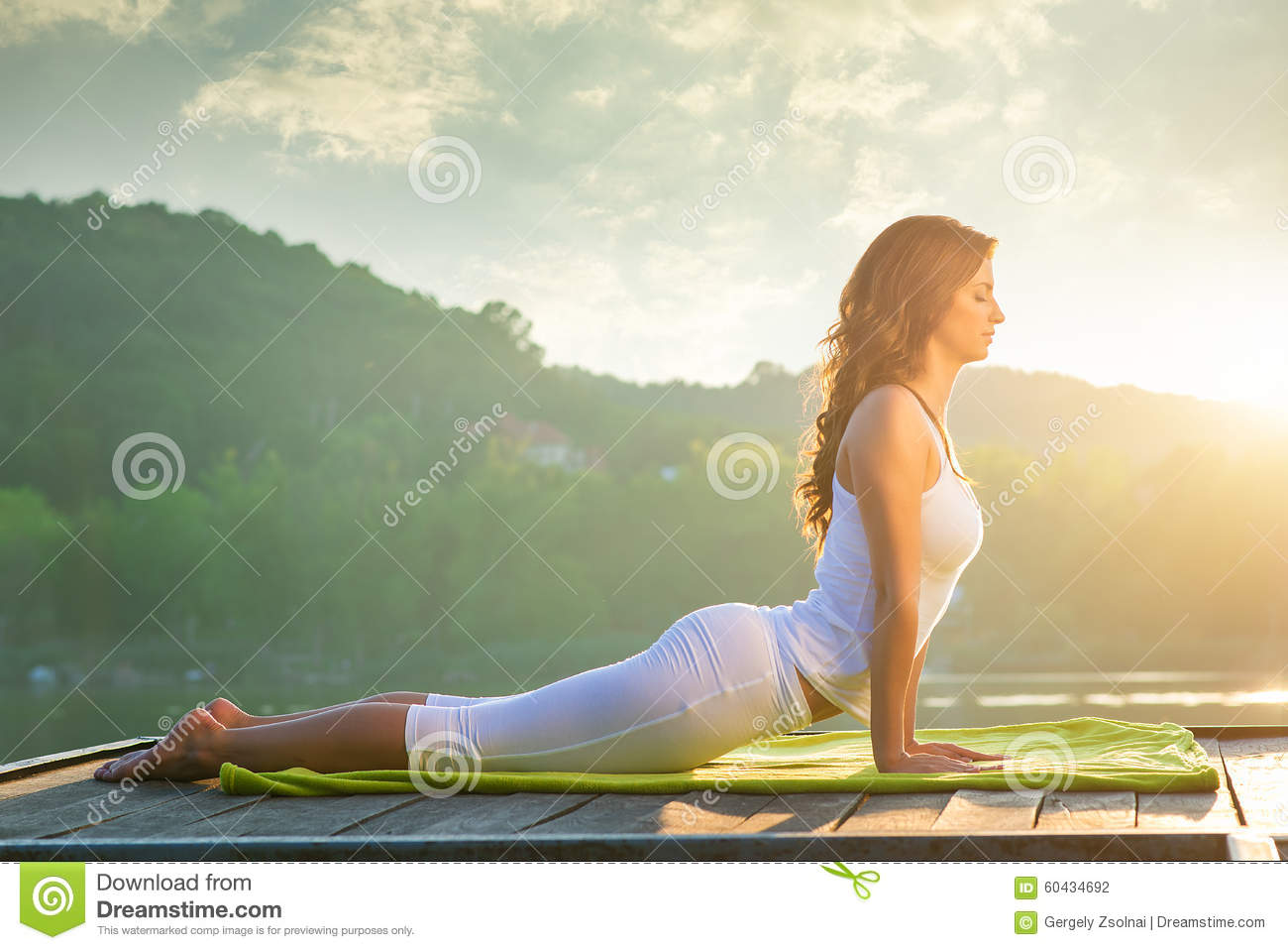 Woman doing yoga on the lake