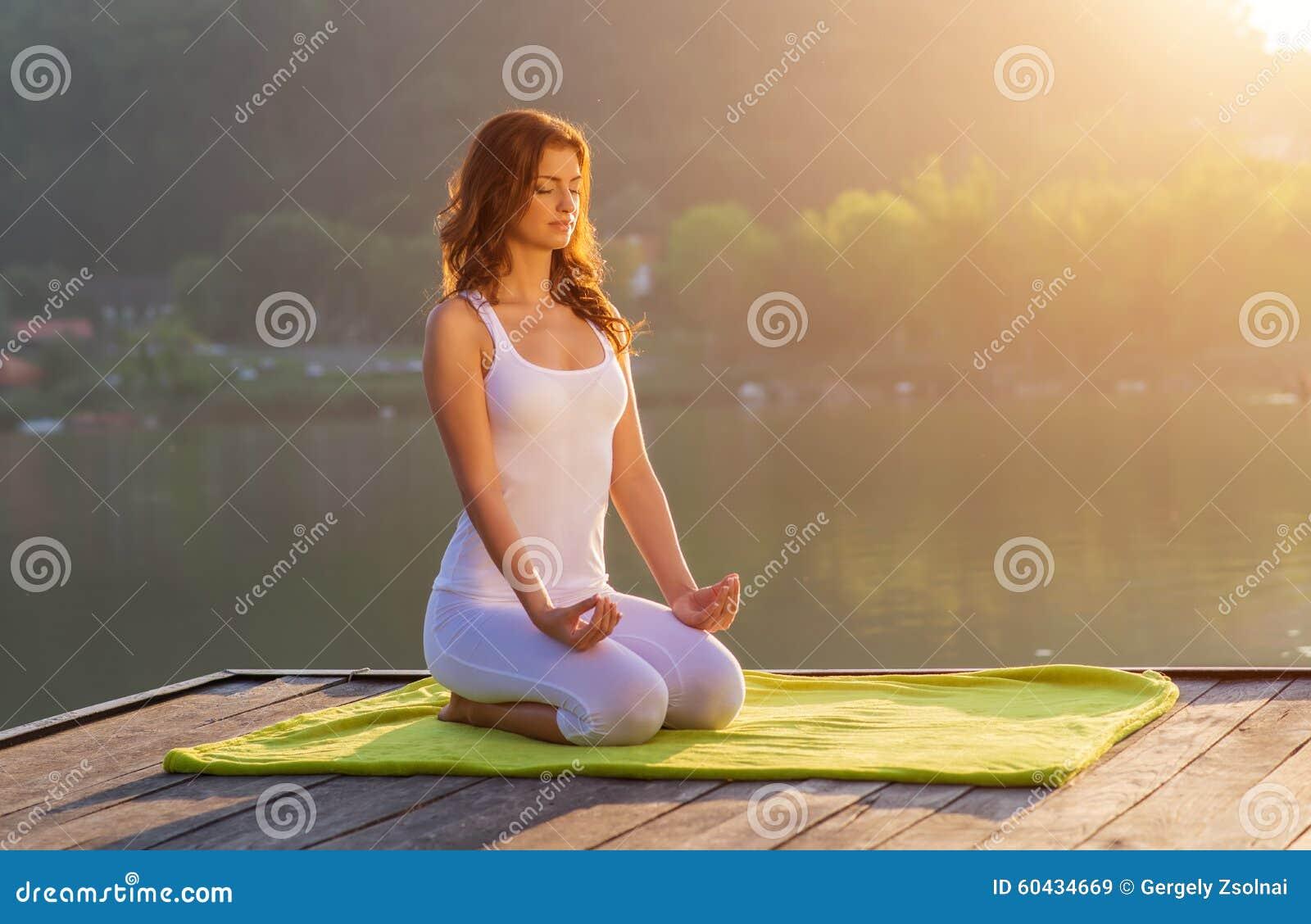 Woman doing yoga on the shore - half figure sitting