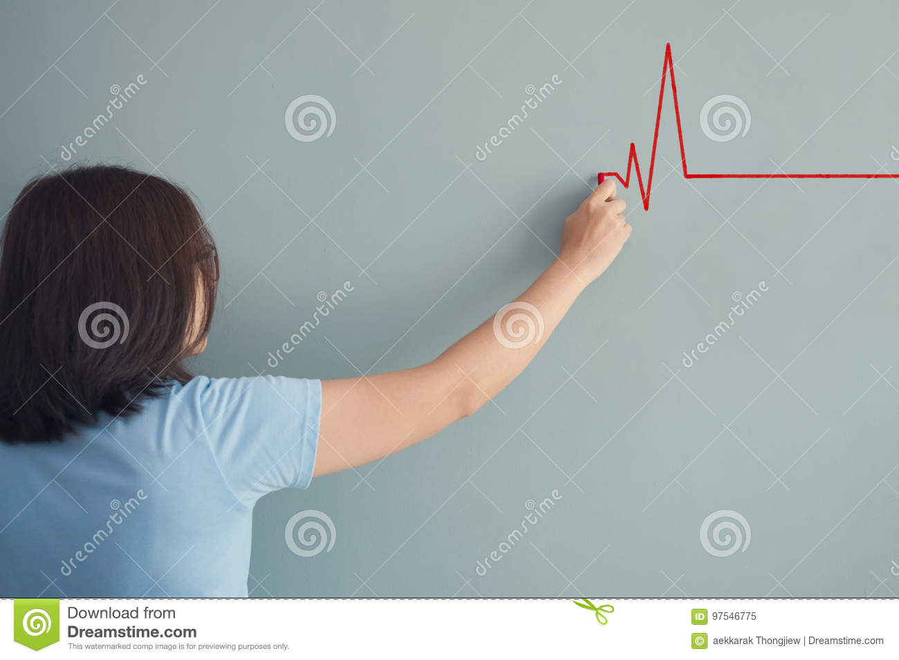 Woman drawing heartbeat with red chalk on wall.