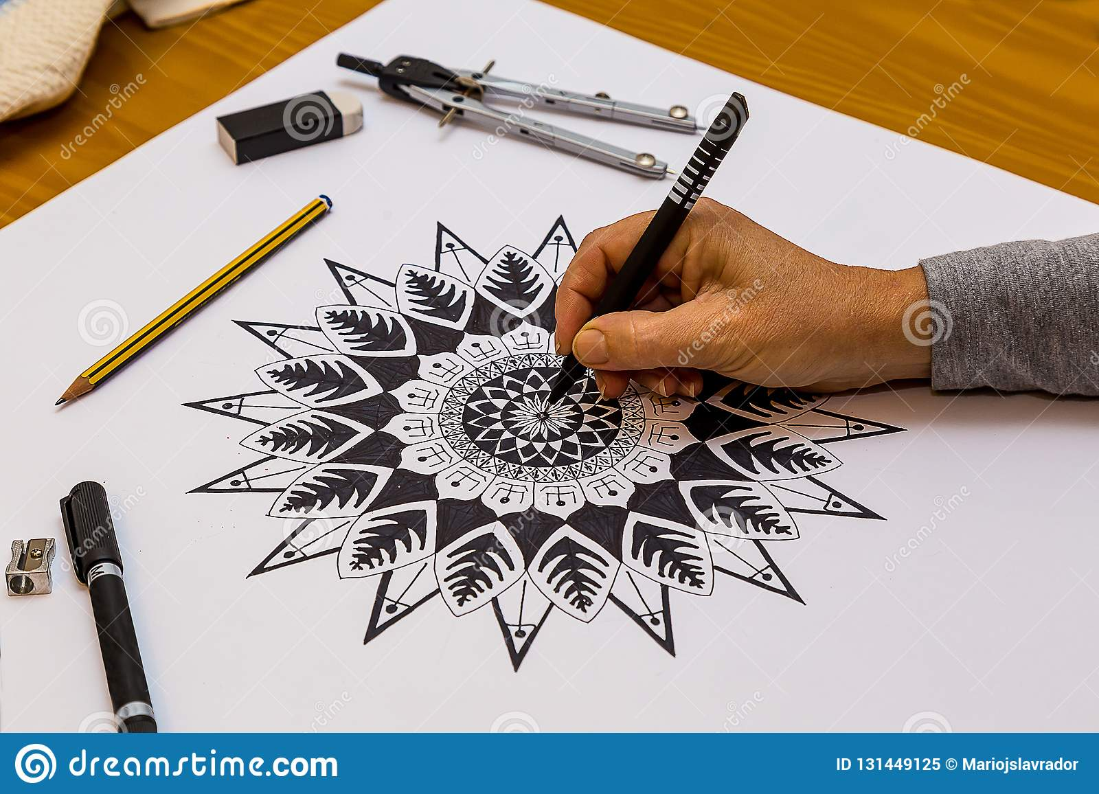 Woman drawing and painting a mandala in black and white