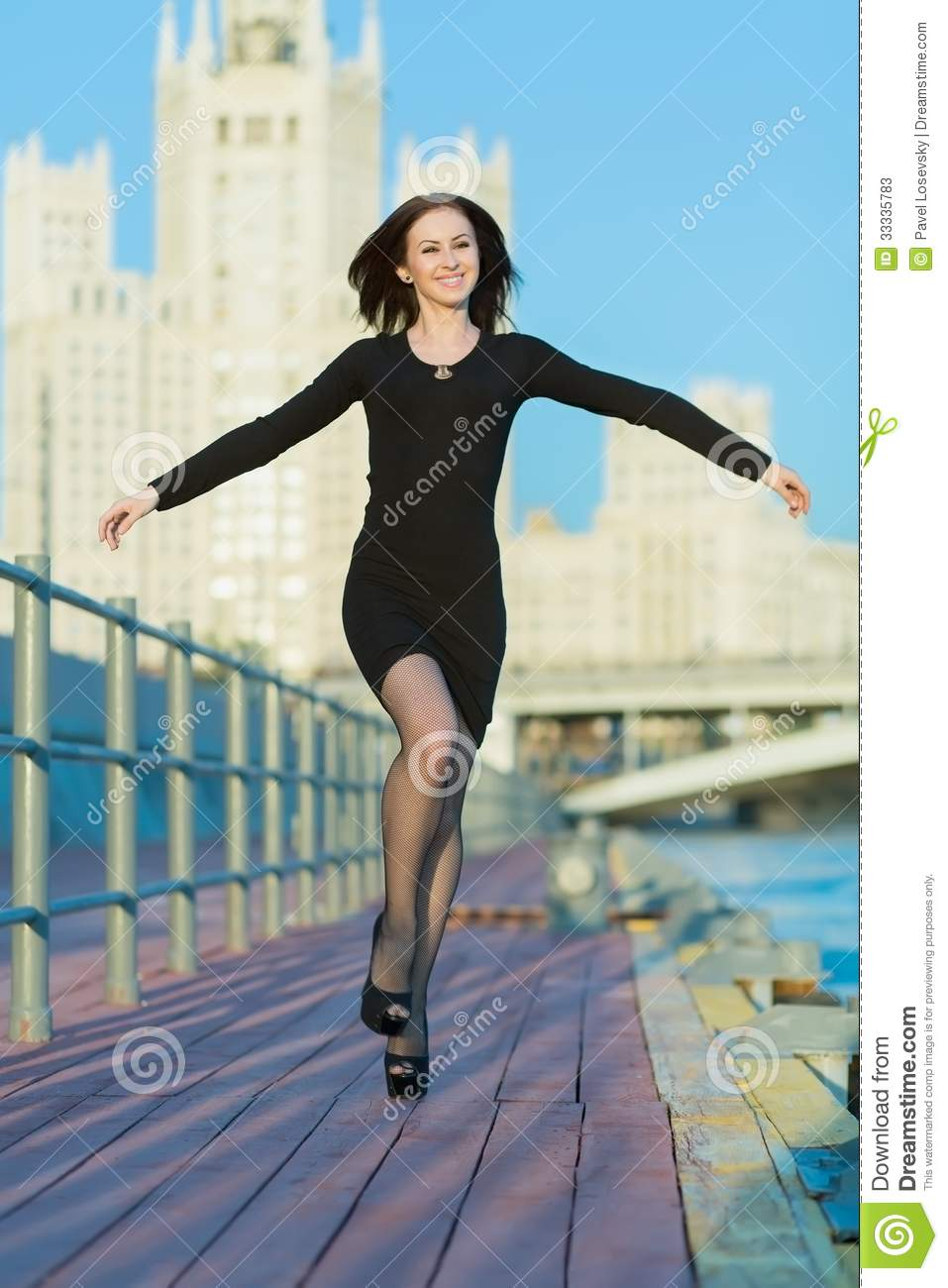 Woman in dress jumping arms outstretched to the sides