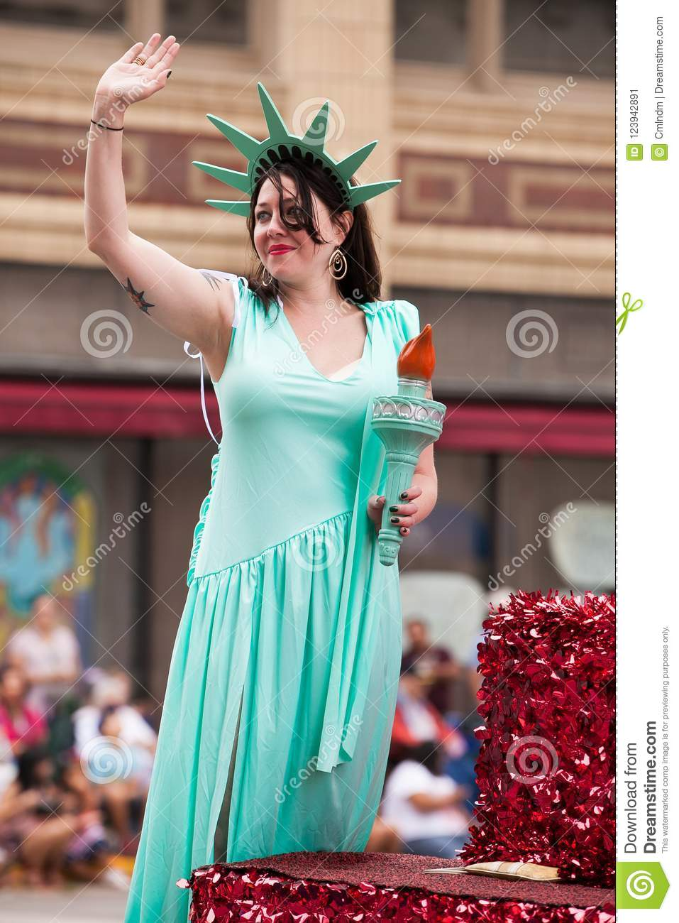 woman dressed as the statue of liberty during fourth of july parade