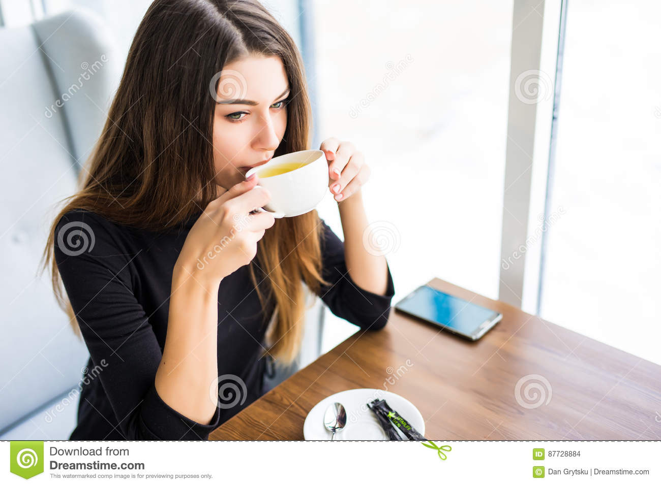 Woman drinking coffee or tea in the morning at restaurant. Closeup portrait of the pretty girl with cup of tea