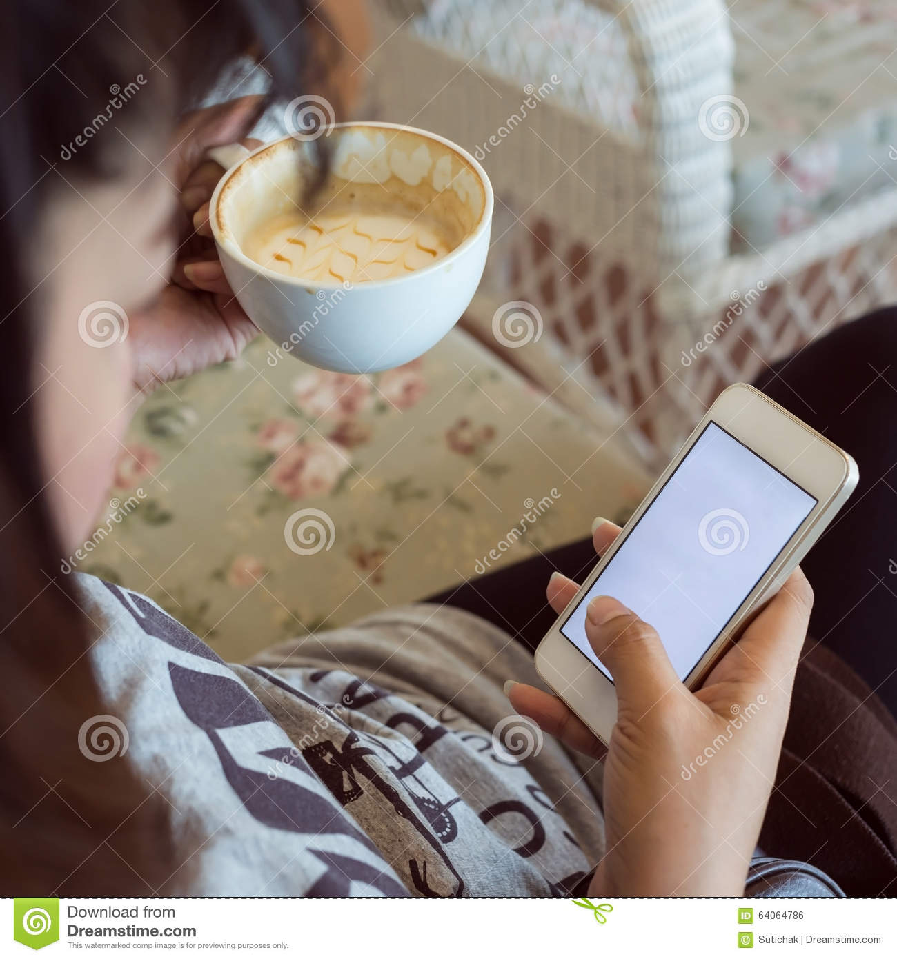 Woman drinking hot coffee in cafe and use a mobile phone