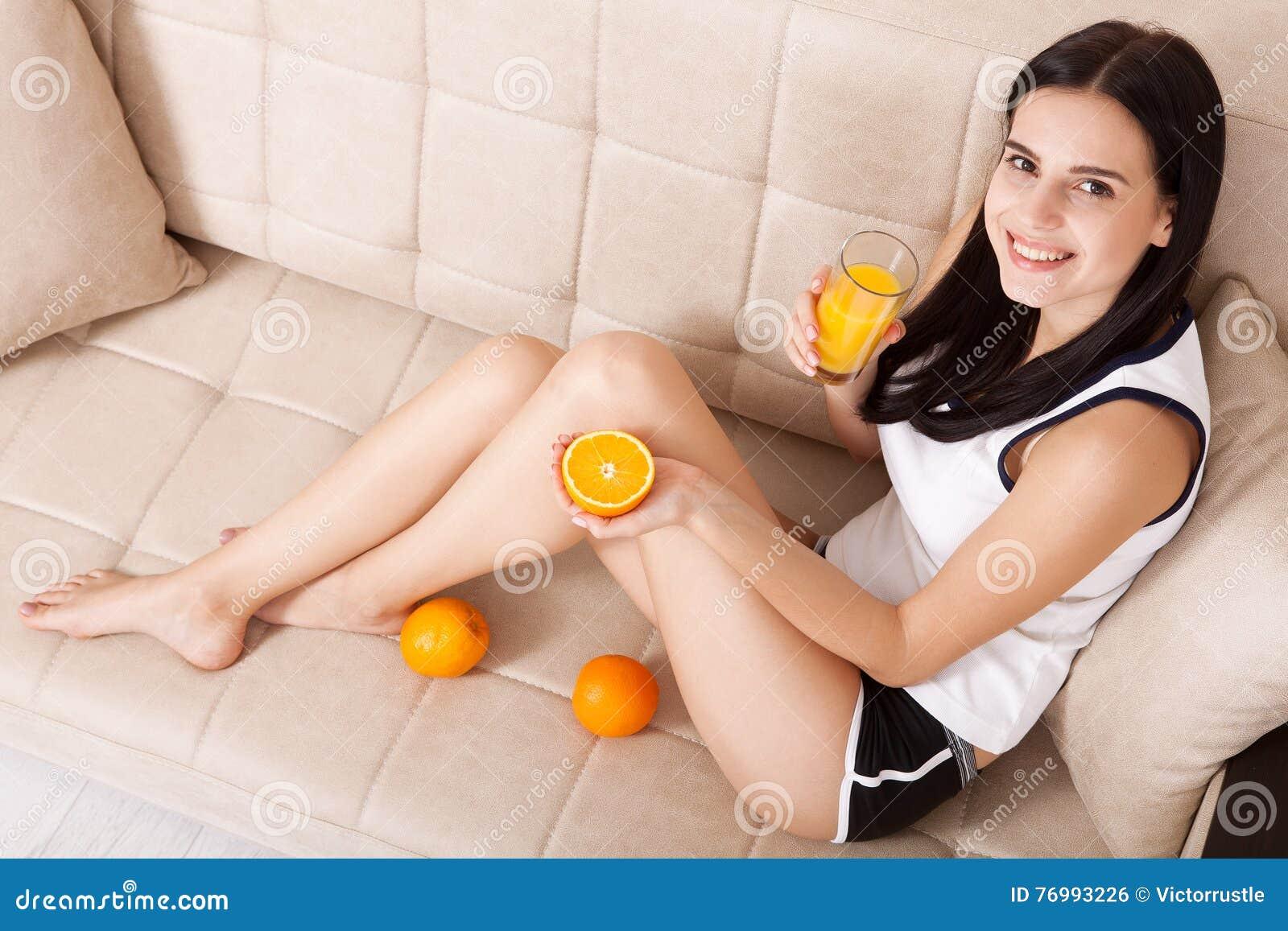 Woman drinking orange juice Beautiful mixed-race Asian, Caucasian model. Unusually, top view.