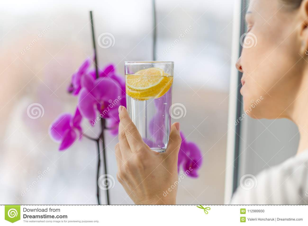 Woman drinking summer refreshing fruit flavored infused water with fresh organic lemon