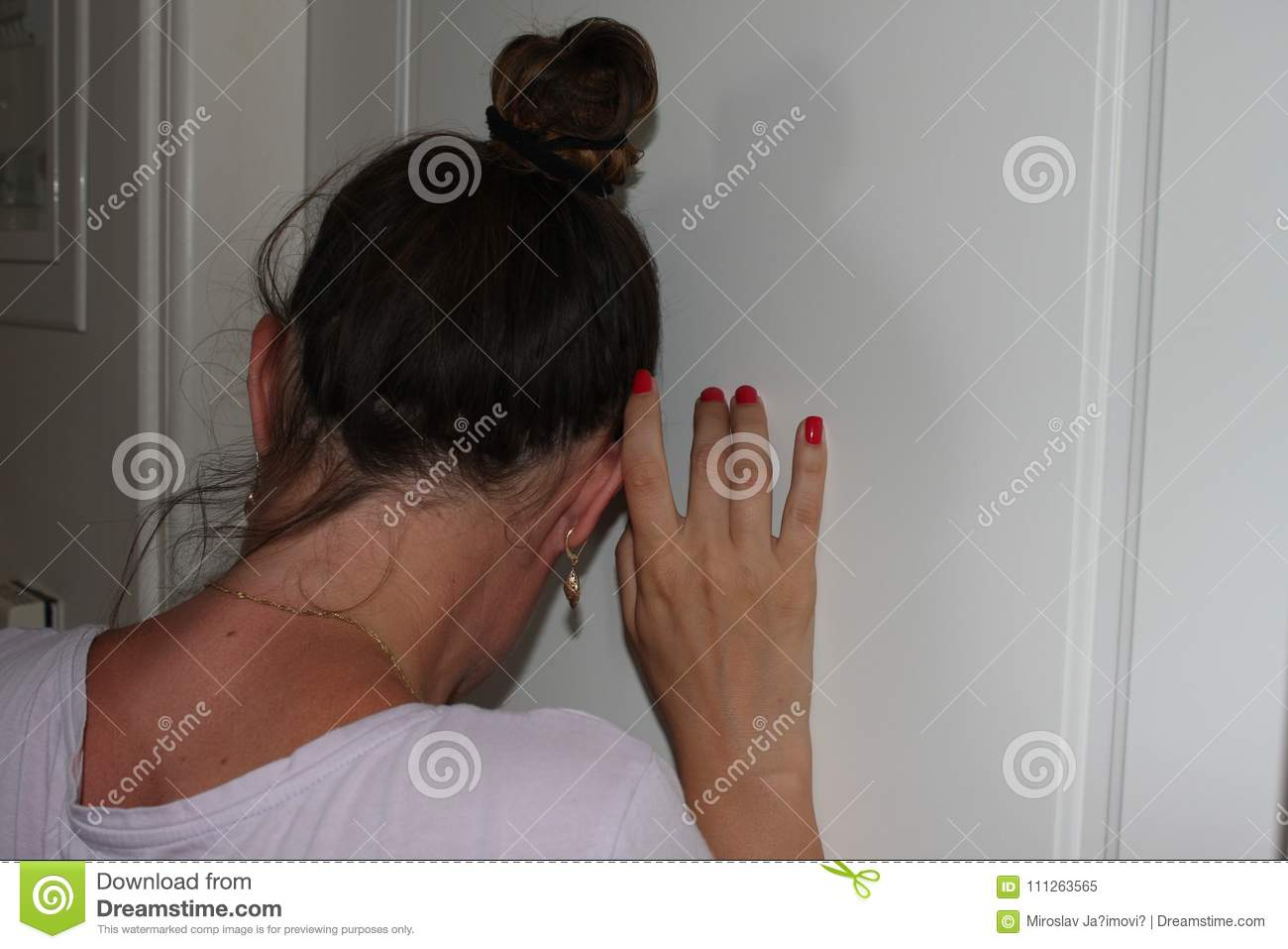 Woman ear pressed to the door with listening what is happening in the next room