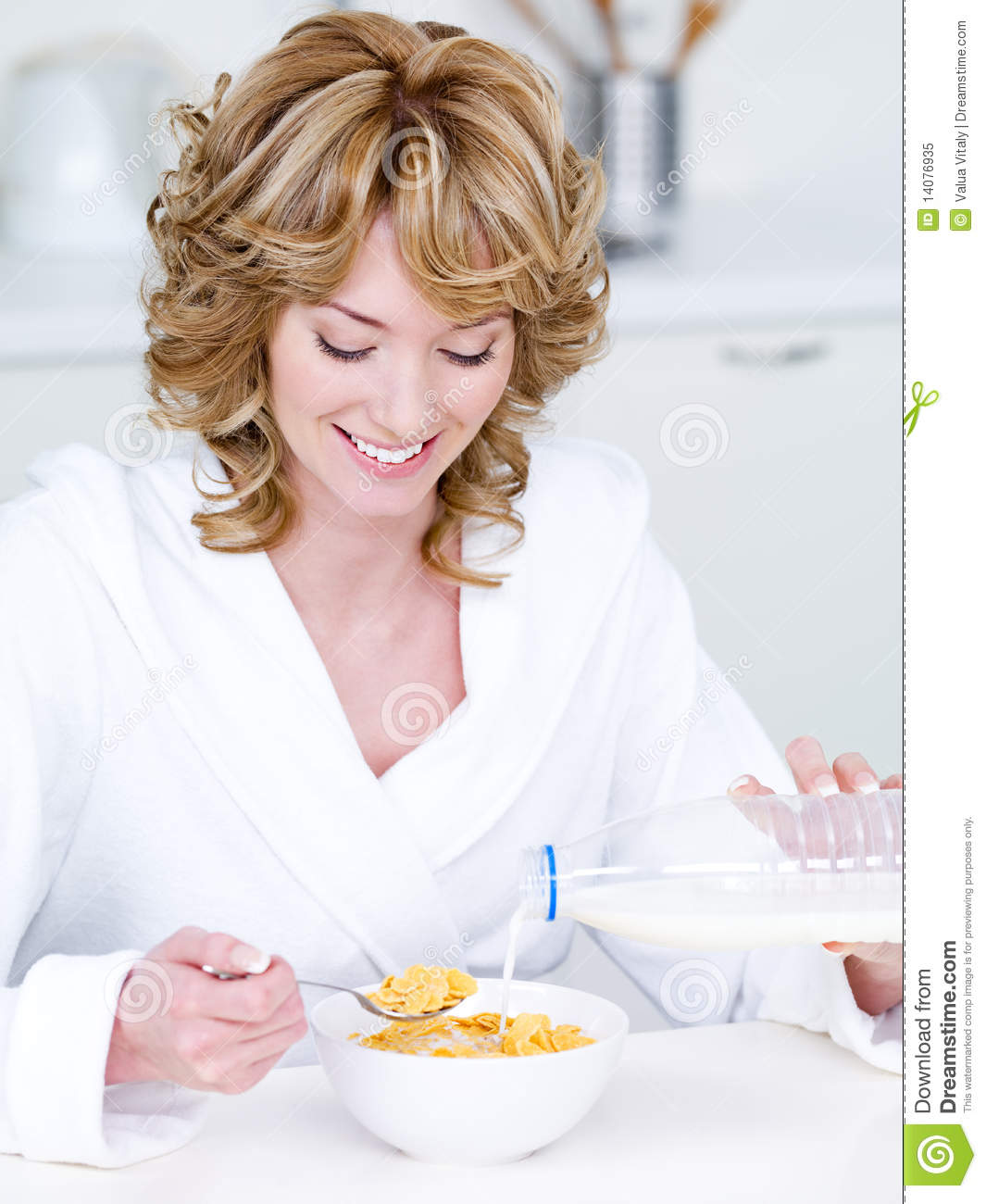 Woman eating corn flakes with milk