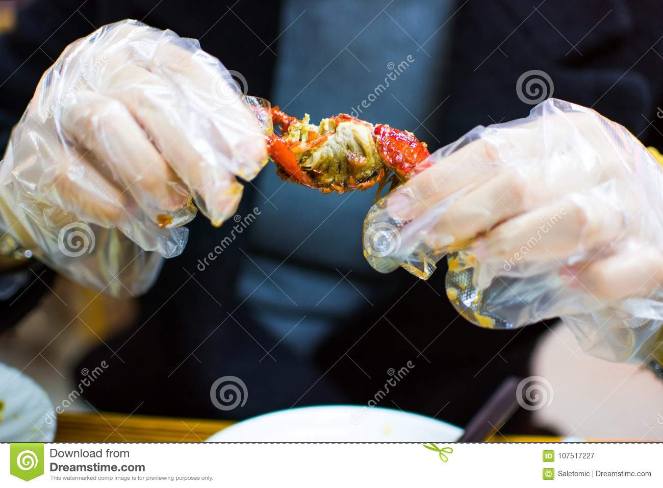 Woman eating a crayfish with plastic gloves