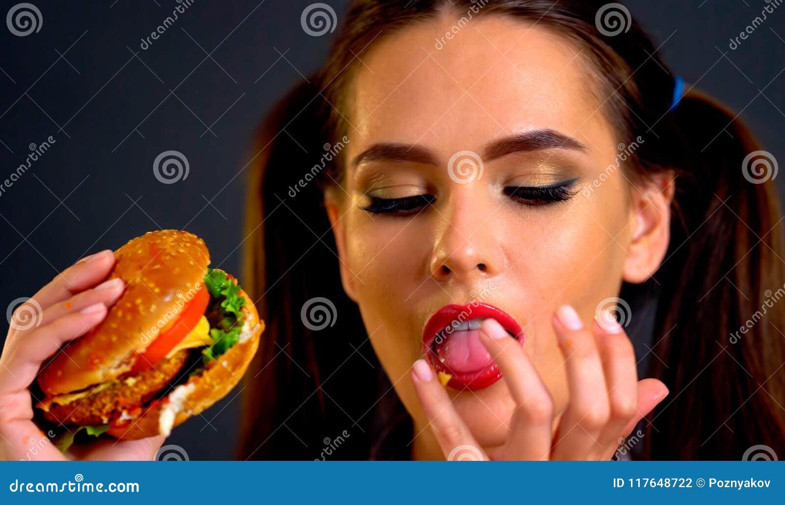 Woman eating hamburger. Girl wants to eat fast food.