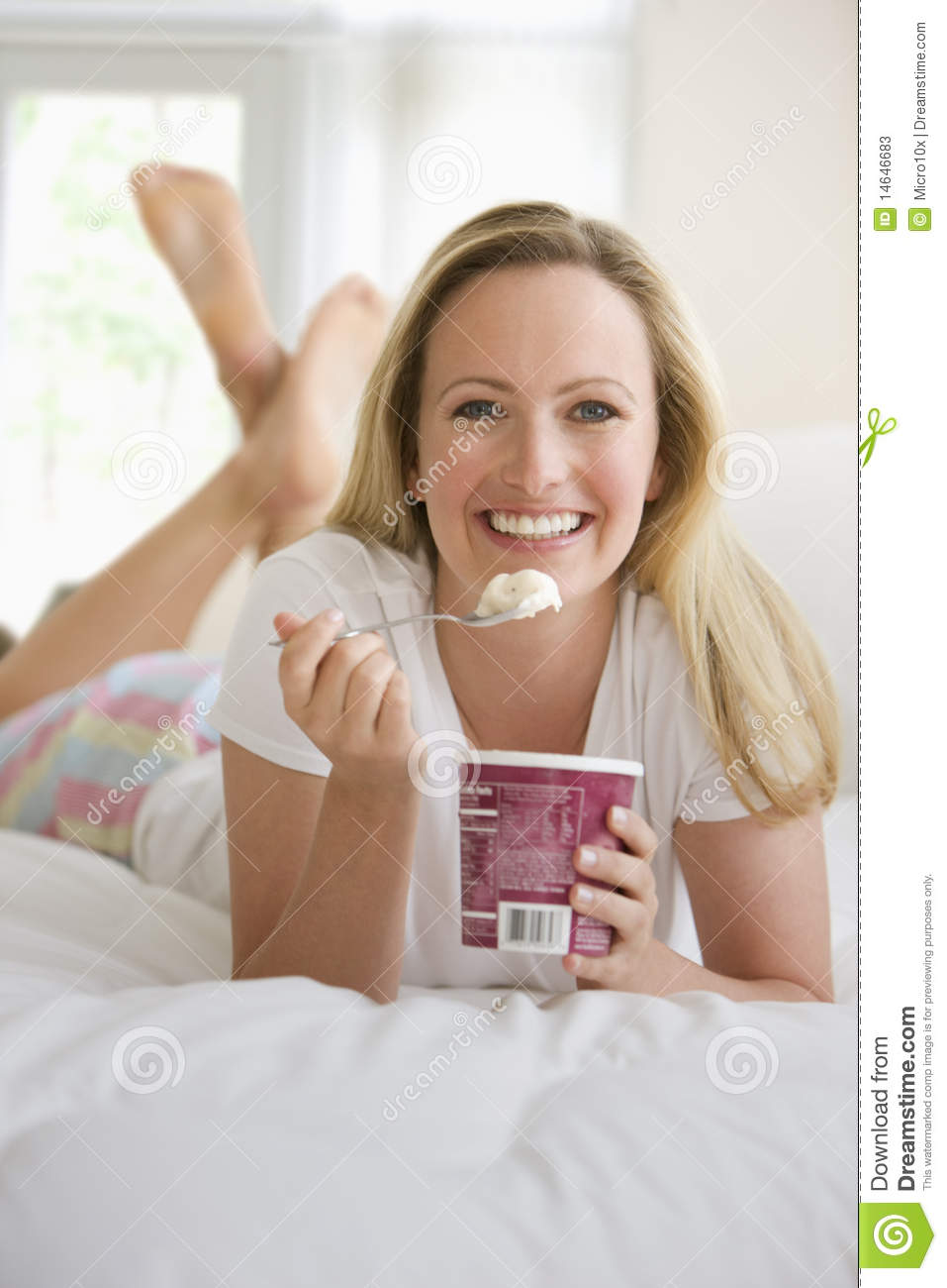 Woman Eating Ice Cream in Bed
